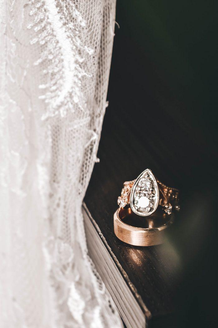 Vintage wedding ring sitting on grooms gold wedding band