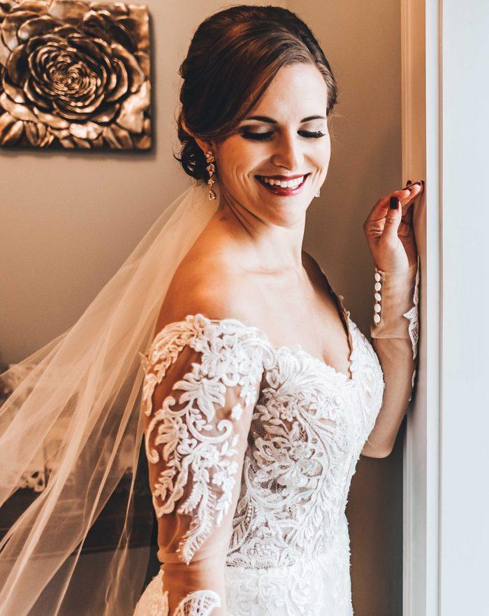 Bride looking over her shoulder standing in front of a brides room window