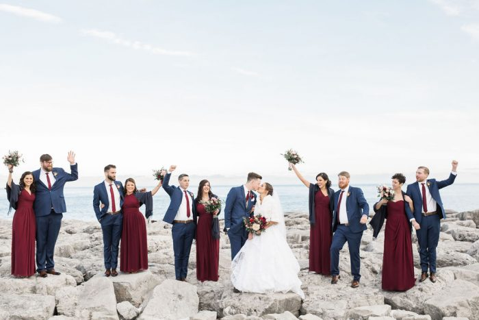 Wedding party standing on rocks in front of Lake Michigan while the bride and groom kiss