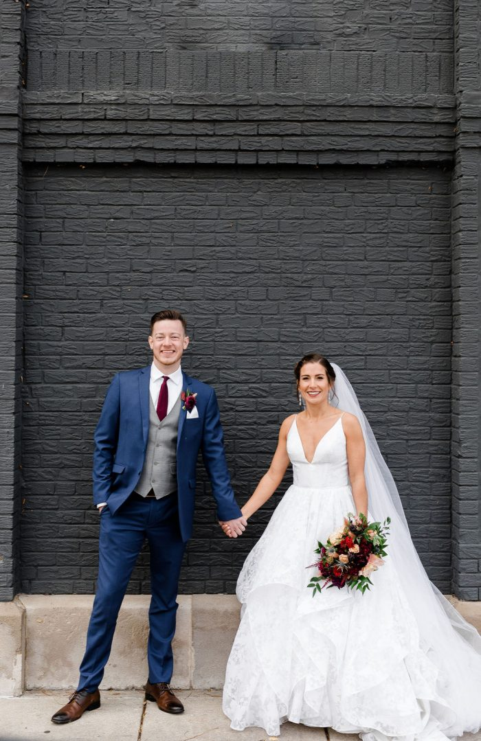Portrait of Bride and Groom smiling in front of a dark charcoal gray brick wall