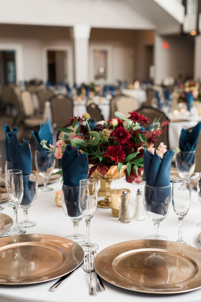 Table setting with navy napkins, gold chargers, and a burgundy centerpiece floral arrangement