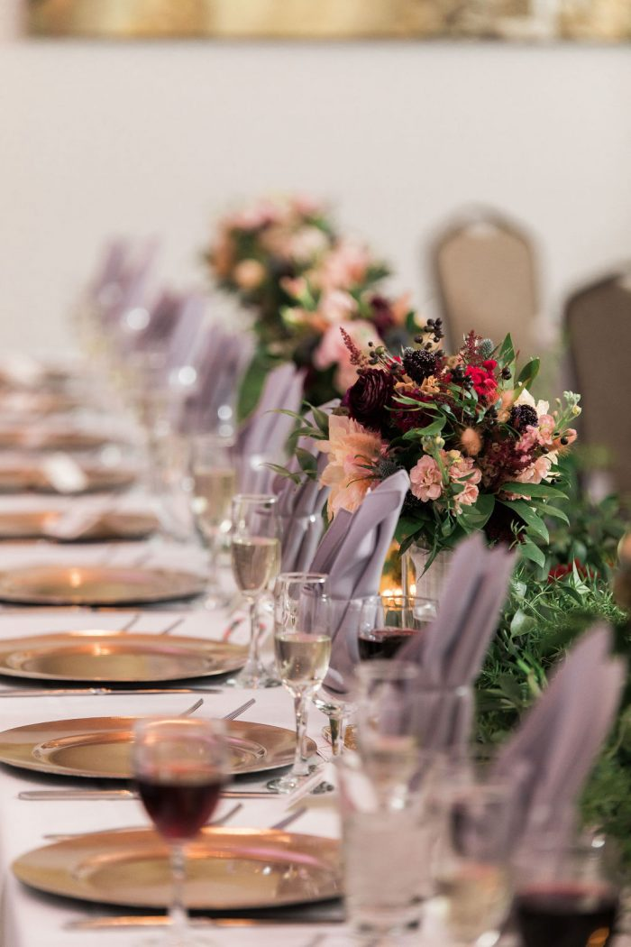 View down head table of champagne flutes, bridesmaids bouquets, and folded gray napkins