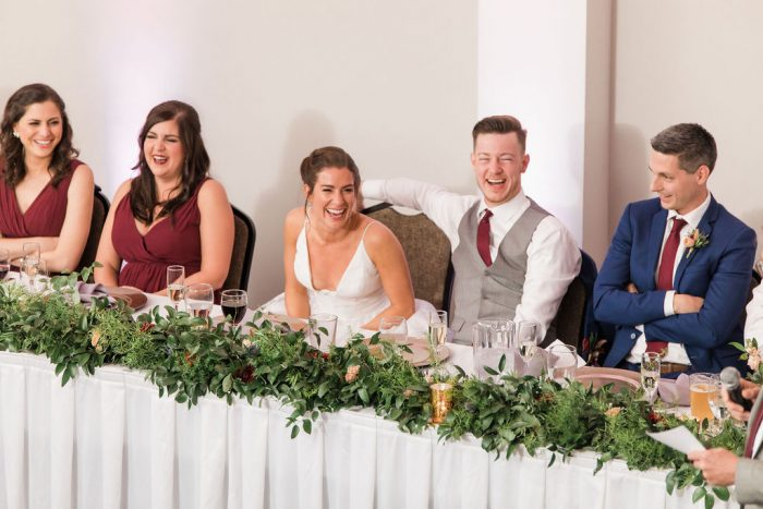 Bride, Groom, and wedding party laughing at head table during toasts