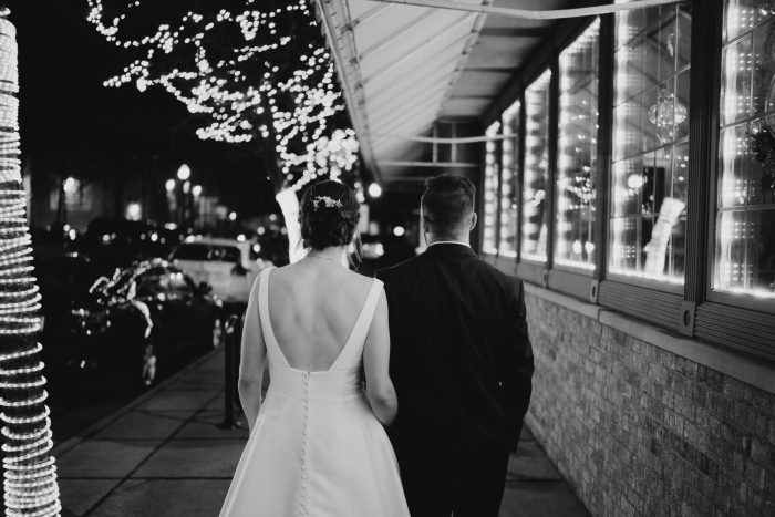 Black and White photo of the bride and groom walking down the sidewalk in Downtown