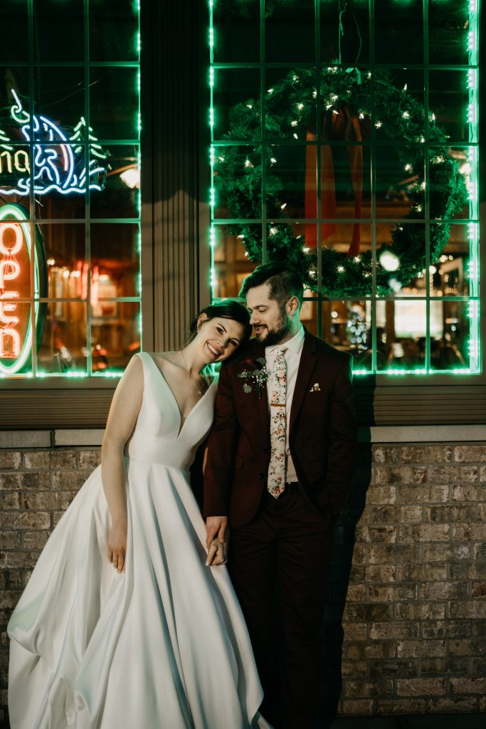 Bride resting her head on the grooms shoulder standing in front of windows glowing with green lights