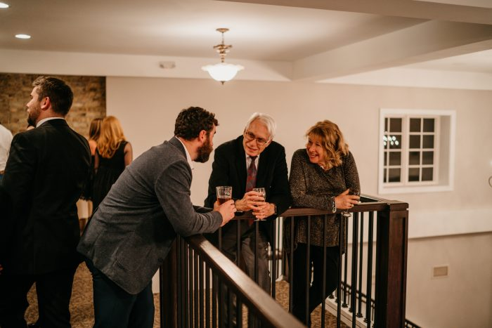 Guests standing with drinks talking over banister in a loft-like balcony