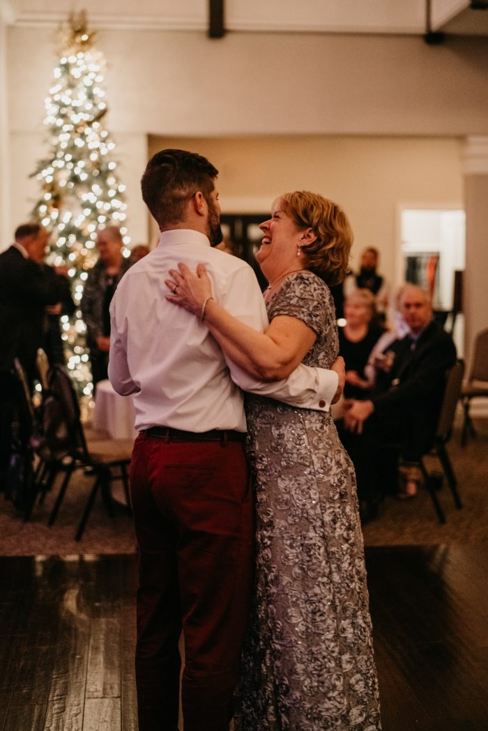 Groom dancing with his mom in front of a holiday tree