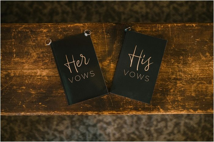 His and hers vow books sitting on antique wood bench