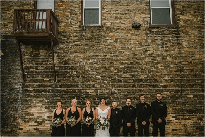 Bridal Party standing in front of exterior exposed brick wall