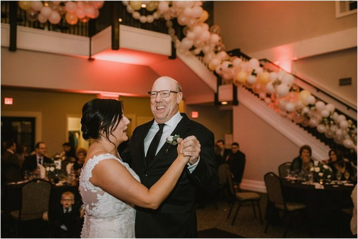 Bride laughing with her dad during their father daughter dance