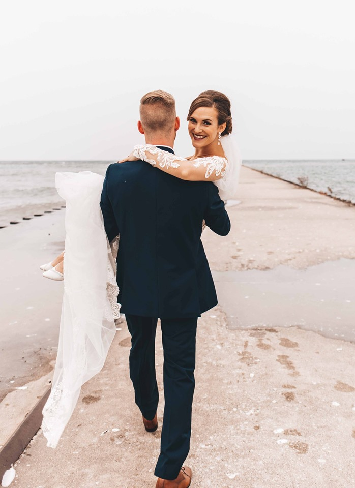 Groom carrying the bride down the pier along Lake Michigan
