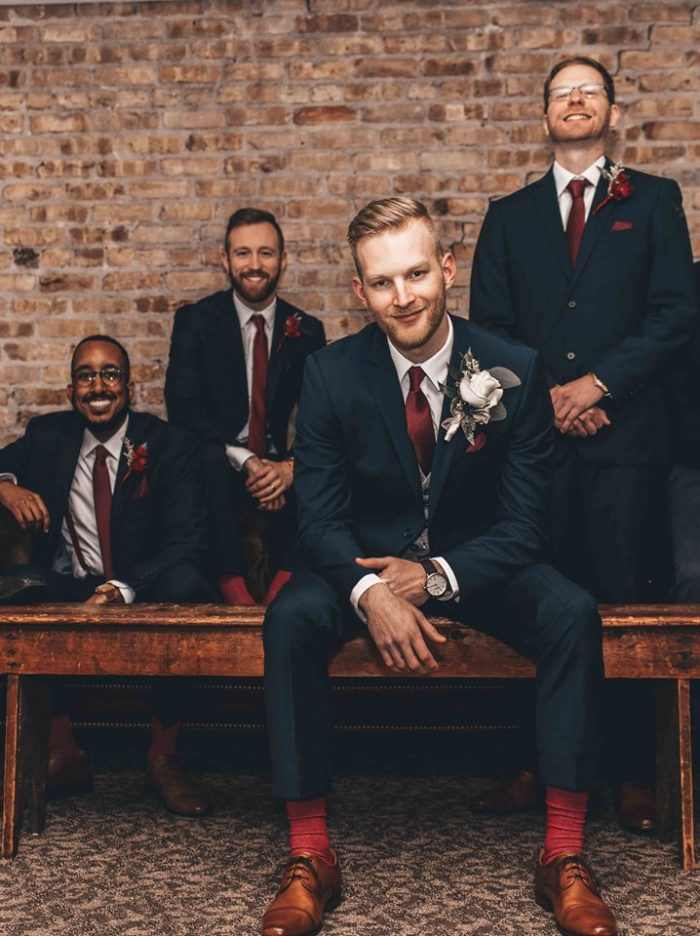 Groom sitting on wooden bench in front of groomsmen near brick wall
