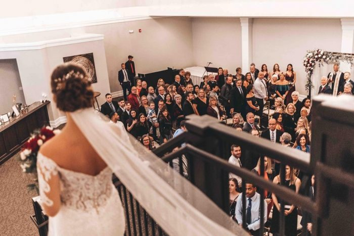 Bride entering down the stairs to her ceremony with the guests reacting