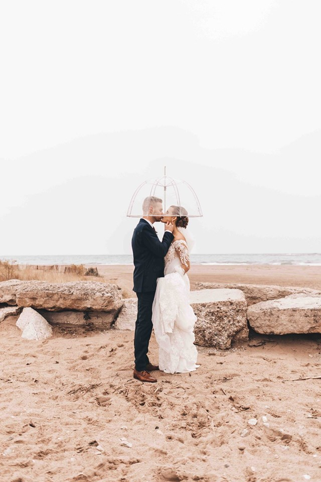 Bride and Groom kissing on the beach under a clear umbrella