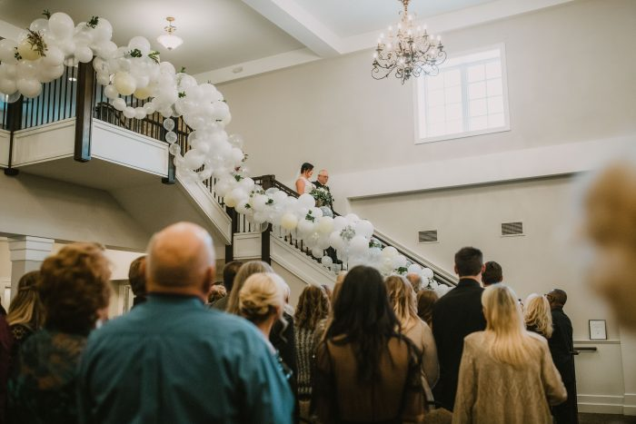 Bride and Dad walking down a Grand Staircase covered in balloons