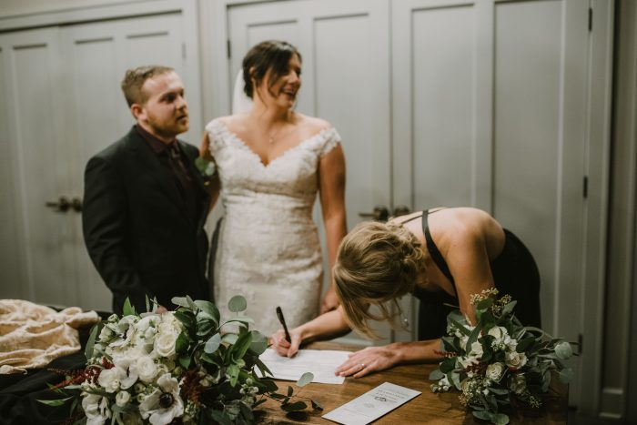 Maid of Honor signing the marriage license with bride and groom smiling