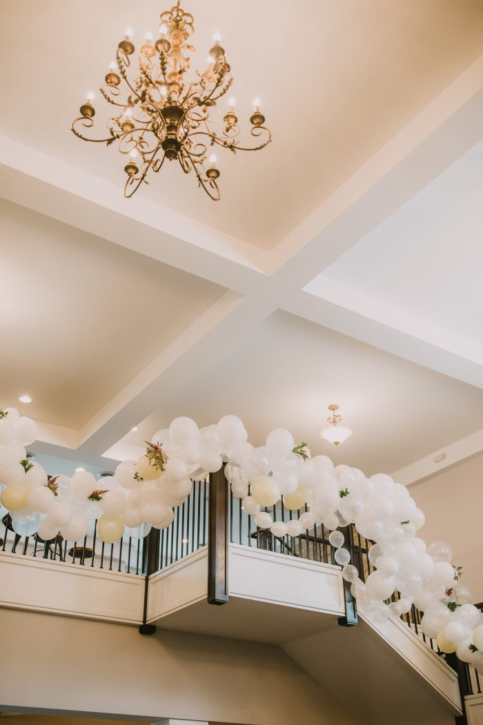 Wedding Venue with tall ceilings, chandeliers, and balloons covering staircase banister