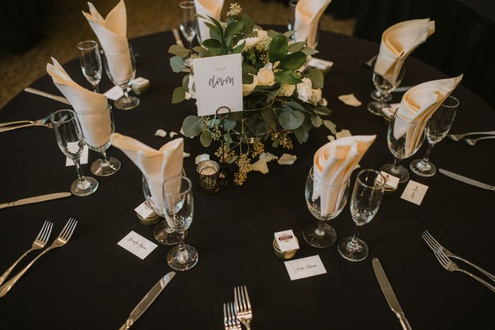 White Roses and Greenery Centerpiece sitting on Black Table Linens with Cream Napkins