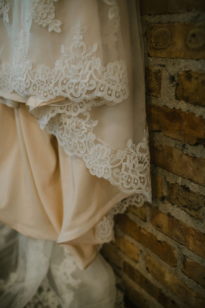 Lace detailing on the bottom of a wedding dress hanging in front of an exposed brick wall