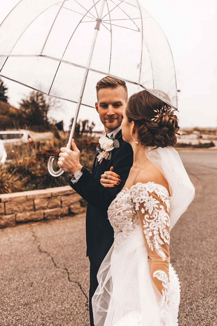 Bride and Groom looking at each other while walking under a clear umbrella