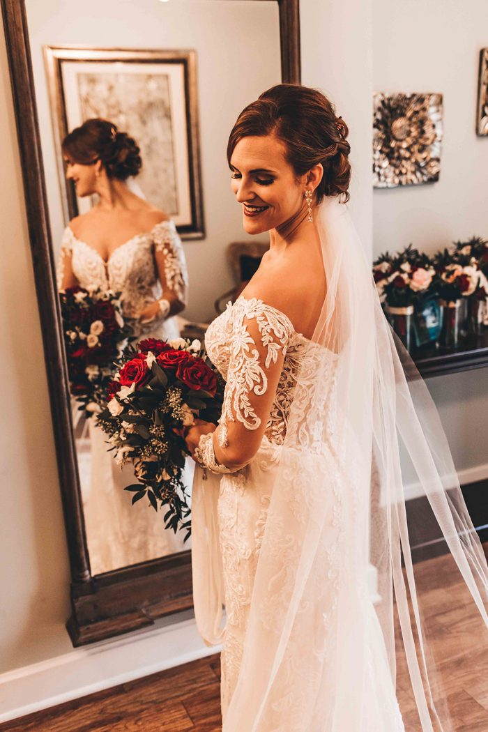 Bride looking down to the floor standing in front of a full length wood framed mirror