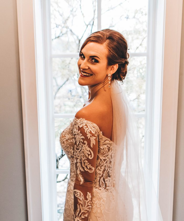 Bride looking back over her shoulder while standing in front of a full length window in the brides room