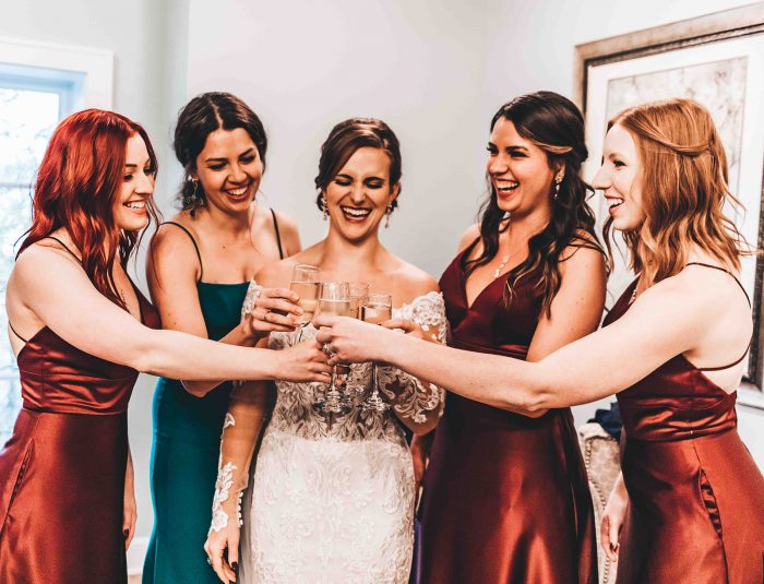 Bride and Bridesmaids clinking champagne flutes together in a 'cheers'