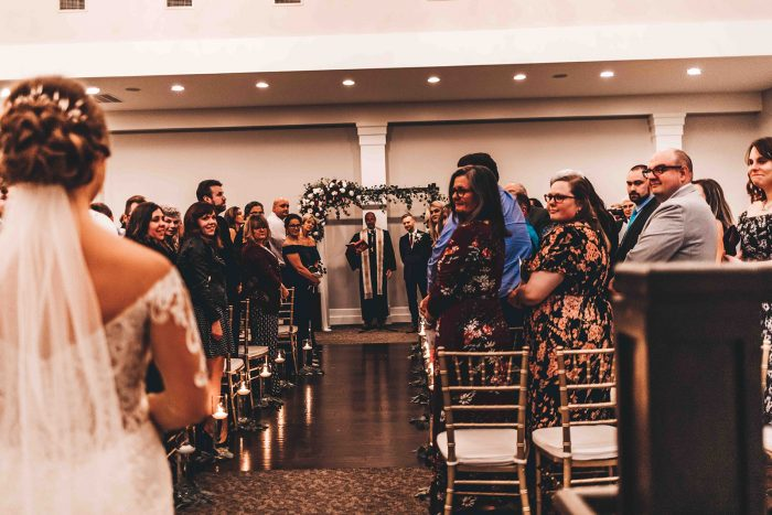 View from behind the bride capturing the guests reaction as she walks down the ceremony aisle