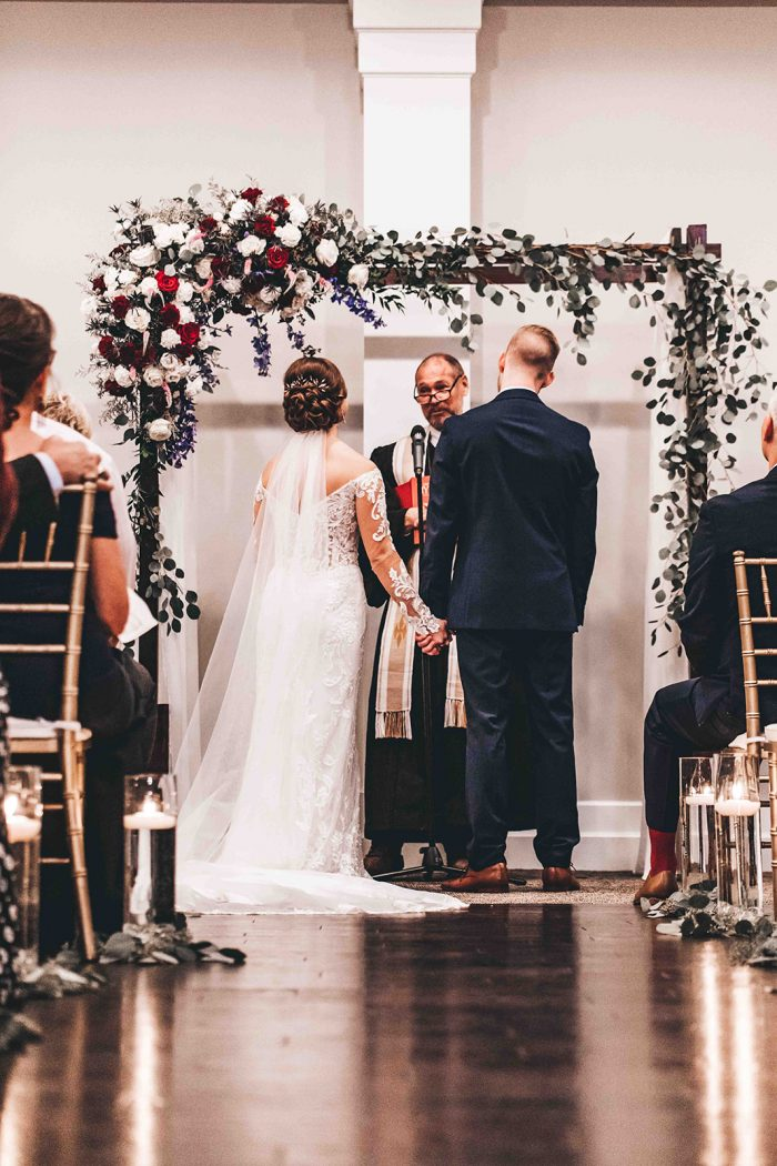 View from behind the bride and groom standing under a floral and wooden ceremony archway