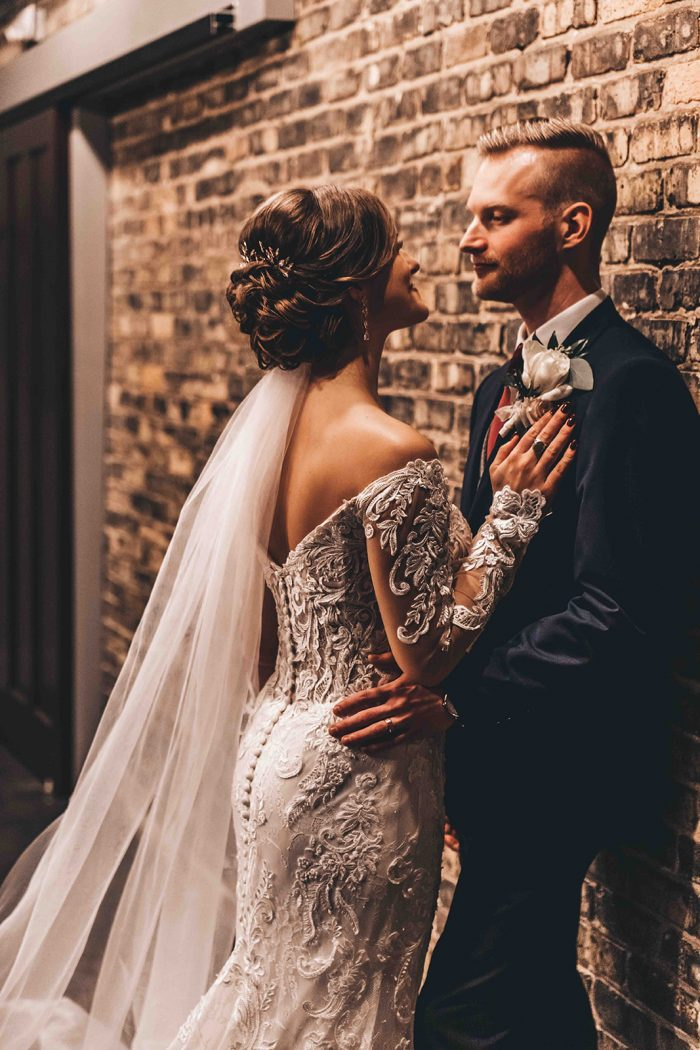 Groom leaning on an exposed brick wall with the bride leaning on his chest