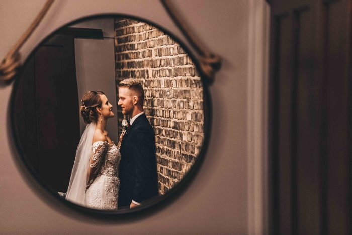 Reflection of the bride and groom in a hanging round mirror