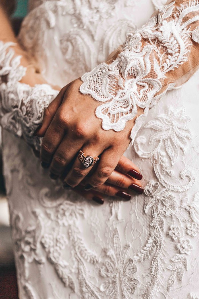Brides holding her hands in front of her lace wedding down showing her vintage wedding ring