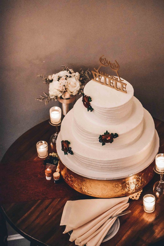 Overhead view of three-tier wedding cake sitting on gold cake stand