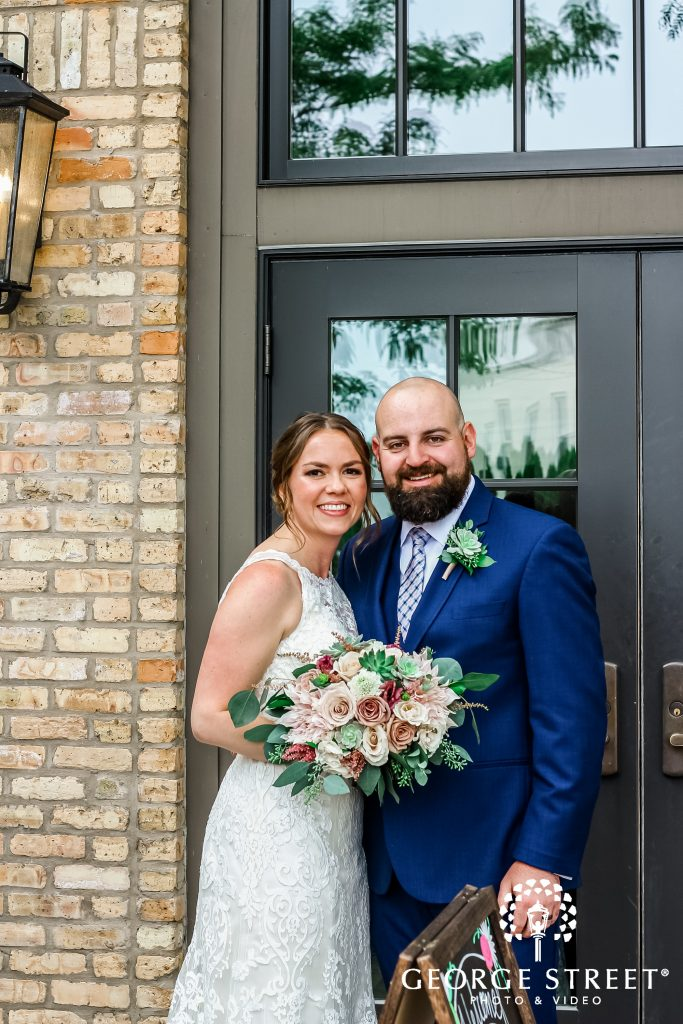 Bride and Groom standing in front of front doors of Circa on Seventh
